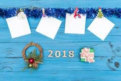 Etiquetas engomadas de papel y ornamentos y juguetes del Año Nuevo en fondo de madera azul Fotos de archivo libres de regalías