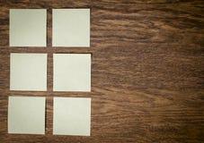 Etiquetas engomadas en la tabla de madera vieja de la tabla Imagen de archivo libre de regalías