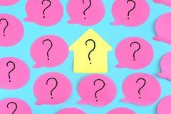 Etiquetas engomadas en un fondo azul Etiquetas engomadas rosadas con los signos de interrogación En el centro está una etiqueta e Fotos de archivo
