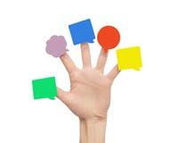 Etiquetas engomadas multicoloras en los fingeres de la mano Fotografía de archivo
