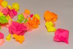 Etiquetas multi-coloridas amarrotadas brilhantes na placa branca do escritório fotografia de stock