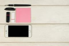 Etiquetas, pena, telefone, cartão de memória Flash em uma tabela de madeira imagens de stock royalty free