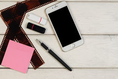 Etiquetas, pena, telefone, cartão de memória Flash, o rolo da câmera em uma tabela de madeira imagens de stock royalty free