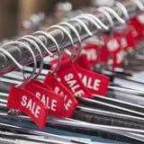 Etiquetas rojas con la venta de la palabra en suspensiones de ropa Imagen de archivo