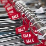 Etiquetas rojas con la venta de la palabra en suspensiones de ropa Imagen de archivo libre de regalías