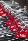 Etiquetas rojas con la venta de la palabra en suspensiones de ropa Foto de archivo libre de regalías