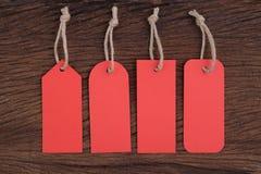 4 etiquetas rojas en la tabla de madera para el texto y la promoción Imagen de archivo