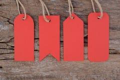 4 etiquetas rojas en la tabla de madera para la venta y el texto Imágenes de archivo libres de regalías