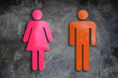 Etiquetas, señoras y hombres en la pared, yeso - rosa anaranjado del icono fotos de archivo
