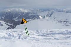Etiquete la advertencia de un acantilado agudo, colocándose en montañas nevosas Foto de archivo libre de regalías