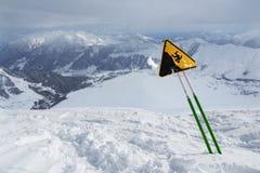 Etiquete la advertencia de un acantilado agudo, colocándose en montañas nevosas Fotos de archivo