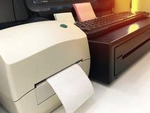 Etiquete o destop themal da impressora e do computador de deslizamento no contador de dinheiro fotografia de stock