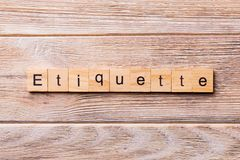ETIQUETTE word written on wood block. ETIQUETTE text on wooden table for your desing, concept royalty free stock photo
