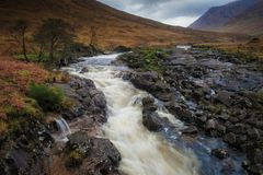 Etive River, Glen Coe, Scotland. The Etive River rushes cascading through the mountains and cutting its way through rocks, with a small waterfall on its edge, on Stock Photo