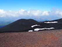 Etna Mount and red ground crater in Sicily, Italy. Etna Mount and red ground crater, tallest active volcano in Europe with clouds in clear blue sky in warm and Royalty Free Stock Photo