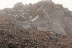 The Etna volcano. The Etna volcano crater. Black Volcanic Earth, Volcanic Lava and Stones. Dense Fog on Mount Etna. Place for. Text. The island of Sicily, Italy royalty free stock photo