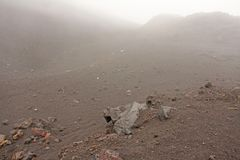 The Etna volcano. The Etna volcano crater. Black Volcanic Earth, Volcanic Lava and Stones. Dense Fog on Mount Etna. Place for. Text. The island of Sicily, Italy royalty free stock image