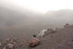 The Etna volcano. The Etna volcano crater. Black Volcanic Earth, Volcanic Lava and Stones. Dense Fog on Mount Etna. Place for. Text. The island of Sicily, Italy stock image