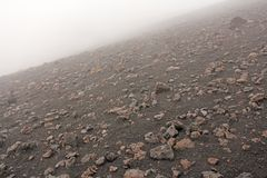 The Etna volcano. The Etna volcano crater. Black Volcanic Earth, Volcanic Lava and Stones. Dense Fog on Mount Etna. Place for. Text. The island of Sicily, Italy stock photography