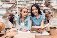 Etniczna azjatykcia dziewczyna i biała dziewczyna otaczająca książkami w bibliotece Ucznie są czytelniczym książką fotografia royalty free