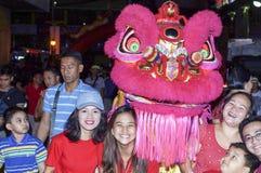 Etniczna Filipińska Chińska poza z Dancingową lew maskotką podczas nowego roku świętowania na ulicie zdjęcia royalty free