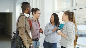 Etniczna grupa cztery ucznia stoi w szerokiej lighty szklistej sala w szkole wyższa opowiada each inny w pozytywnym sposobie zdjęcie wideo