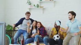 Etniczna grupa ogląda futbolowego mistrzostwo na TV wpólnie w domu przyjaciół sportów fan z Argentyńskimi flaga zbiory wideo
