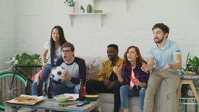 Etniczna grupa przyjaciół sportów fan z austriakiem zaznacza dopatrywania futbolowego mistrzostwo na TV wpólnie w domu i zbiory