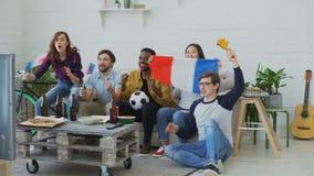 Etniczna grupa przyjaciół sportów fan z francuzem zaznacza dopatrywania futbolowego mistrzostwo na TV wpólnie w domu i zdjęcie wideo