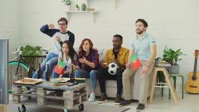 Etniczna grupa przyjaciół sportów fan z portugalczykiem zaznacza dopatrywania futbolowego mistrzostwo na TV wpólnie w domu zbiory