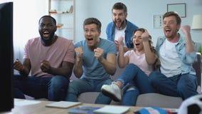 Etniczna grupa przyjaciele ogląda mecz futbolowego w domu, świętuje cel zbiory