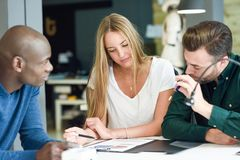 Etniczna grupa trzy młodzi ludzie studiuje wpólnie zdjęcia royalty free