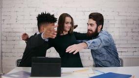 Etniczna różnorodna biznes drużyna obejmuje each inny podczas gdy siedzący przy stołem w nowożytnym biurze Slowmotion strzał zdjęcie wideo