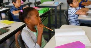 Etniczna szko?a ?artuje studiowanie przy biurkiem w sali lekcyjnej przy szko?? 4k zdjęcie wideo