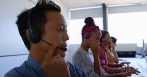 Etniczni klient sprzedaży kierownictwa opowiada na słuchawki w nowożytnym biurze 4k zbiory