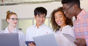 Etniczni ludzie biznesu dyskutuje nad laptopem i cyfrow? pastylk? w nowo?ytnym biurze 4k zdjęcie wideo