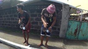 Etniczni miejscowi młodzi człowiecy bije improwizującego bęben błagać dla datków na drodze zdjęcie wideo