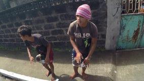Etniczni miejscowi młodzi człowiecy bije improwizującego bęben błagać dla datków na drodze zbiory