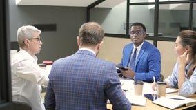 Etniczni partnery biznesowi dyskutuje pieniężną strategię na odprawie zbiory