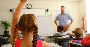 Etniczni schoolkids podnosi ręki podczas gdy siedzący przy biurkiem w sali lekcyjnej przy szkołą 4k zdjęcie wideo
