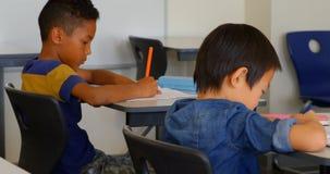 Etniczni schoolkids studiuje przy biurkiem w sali lekcyjnej przy szkołą 4k zbiory wideo
