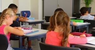 Etniczni schoolkids studiuje przy biurkiem w sali lekcyjnej przy szko?? 4k zdjęcie wideo