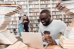 Etniczny amerykanina afrykańskiego pochodzenia facet otaczający książkami w bibliotece Uczeń używa laptop i pije kawę obrazy stock