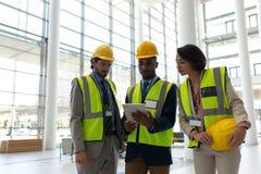 Etniczny biznesowy architekt dyskutuje nad cyfrową pastylką przy biuro lobby zdjęcie stock