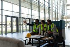 Etniczny biznesowy architekt pokazuje i dyskutuje nad błękitnym drukiem przy biuro lobby fotografia stock