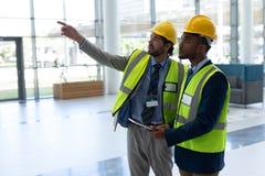 Etniczny biznesowy architekt pokazuje i dyskutuje z each inny podczas gdy stojący przy biurowym lobb zdjęcie stock