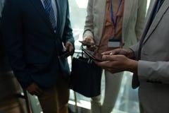 Etniczny biznesowy kolega dyskutuje nad cyfrową pastylką w windzie obrazy stock