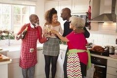 Etniczny dorosły rodzinny uścisk i robi grzance z szampanem świętować na święto bożęgo narodzenia podczas gdy przygotowywający go zdjęcie royalty free