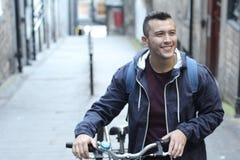 Etniczny mężczyzny przewożenia bicykl na piętrze zdjęcie royalty free