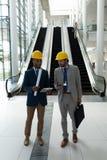 Etniczny męski architekt dyskutuje nad cyfrową pastylką przy biuro lobby zdjęcie stock